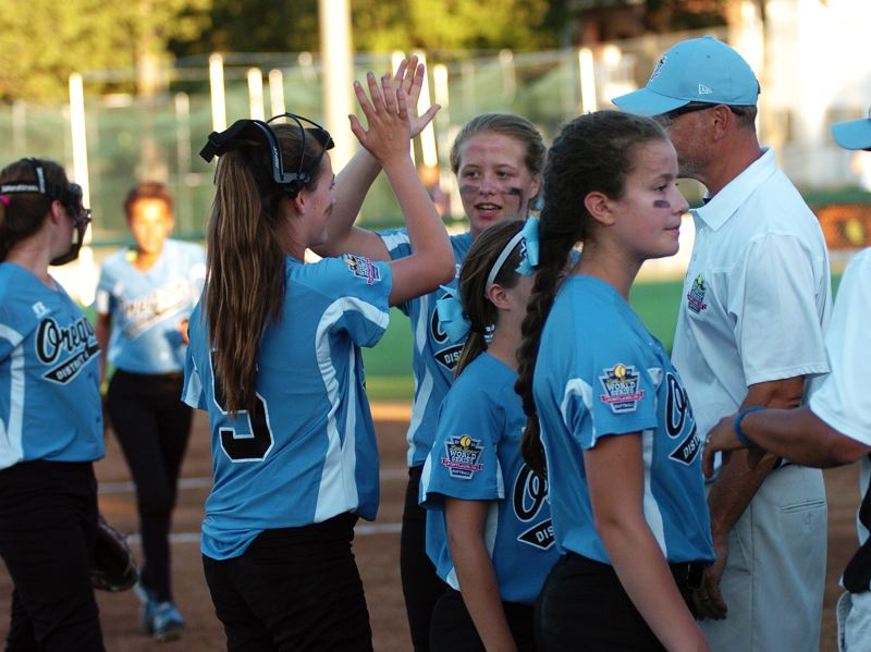 Photo Credit: DAN BROOD - Tigard/TC pitcher Elizabeth Hillier (left) gives a high five to teammate Emily Harms during the team's World Series game with Georgia.