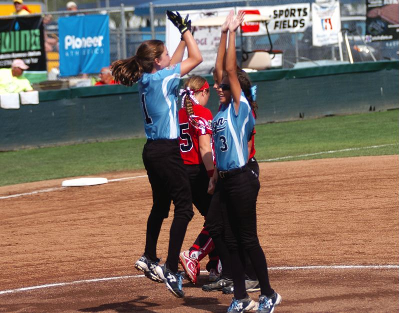 Photo Credit: DAN BROOD - Tigard/TC catcher Alexis Klum (left) jumps up to slap hands with Tia Cordts prior to the World Series fifth-place game with Canada.