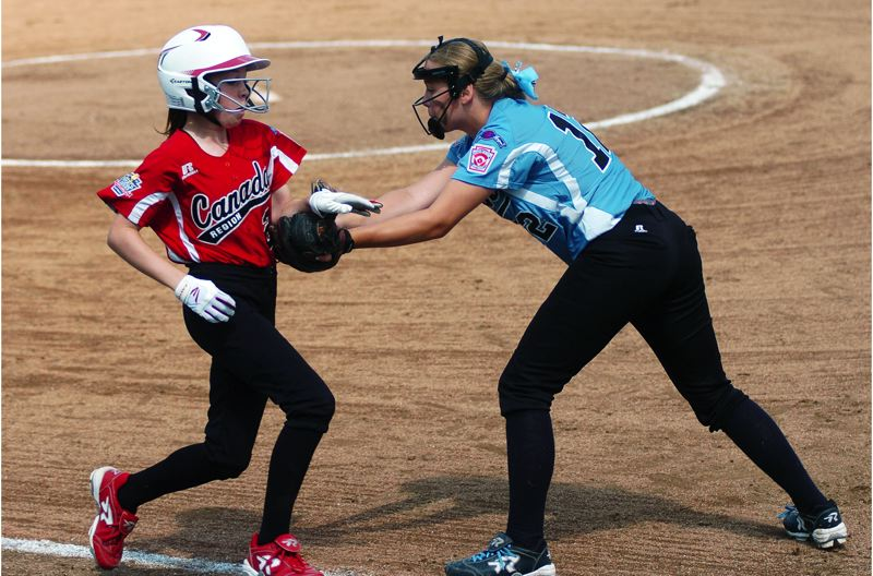 Photo Credit: DAN BROOD - TNT first baseman Emily Harms (right) tags out Canada's Leann Rompain.