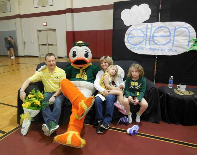 Photo Credit: COURTESY OF JENESSA ROSE - Following an all-school assembly themed 'The Ellen Show' to honor SHS counselor Jeneva Rose in her fight against brain cancer, she sits on a couch with her husband Tim and daughters Jazlyn (on her lap) and Jenessa along with Puddles, the University of Oregon mascot.