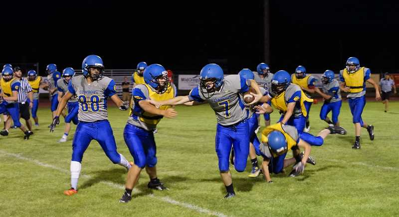 Photo Credit: PHOTO CONTRIBUTED BY DOUG SMITH - Blake Bartels stiff-arms a defensive player en route to a big run during the annual Football Blue & Gold Scrimmage Saturday night. Bartels is expected to be the Cowboys' starting quarterback this year.