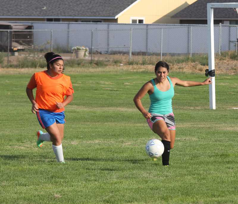 Photo Credit: JEFF WILSON/THE PIONEER - Freshman Michell Galan, left, tries to run down Coral Reyes during a Madras girls' soccer practice last week. This year's team is short on numbers, but expects to compete well in the new Tri-Valley Conference.