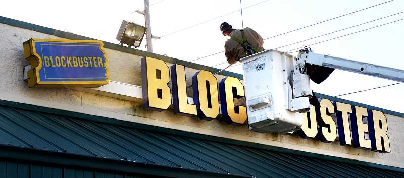 Photo Credit: POST PHOTO: LAURA KNUDSON  - A worker begins to remove the Sandy Blockbuster sign that will be hung two shops over.