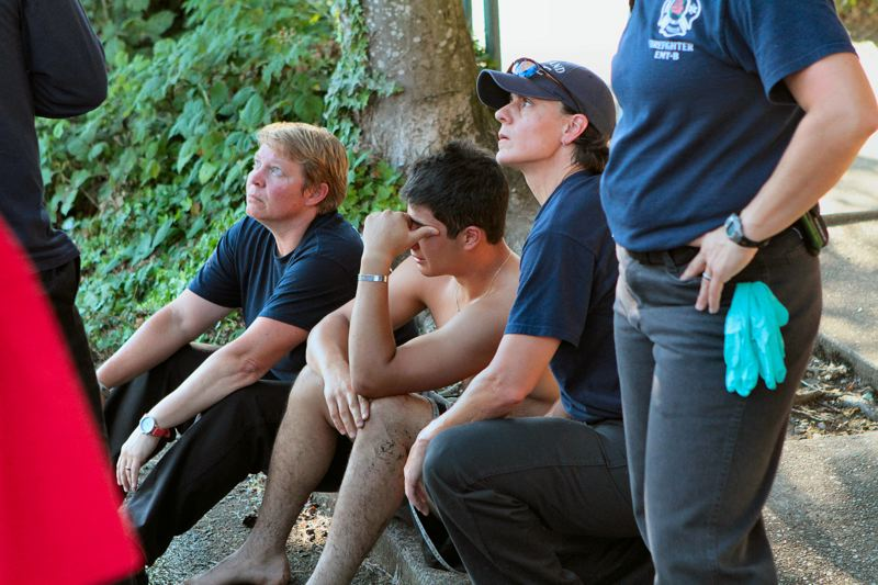 Photo Credit: DAVID F. ASHTON - Firefighters from Westmorelands Station 20 comfort a friend who was swimming with the young man who had just drowned in the Willamette River near the east bank, just south of the Sellwood Bridge.