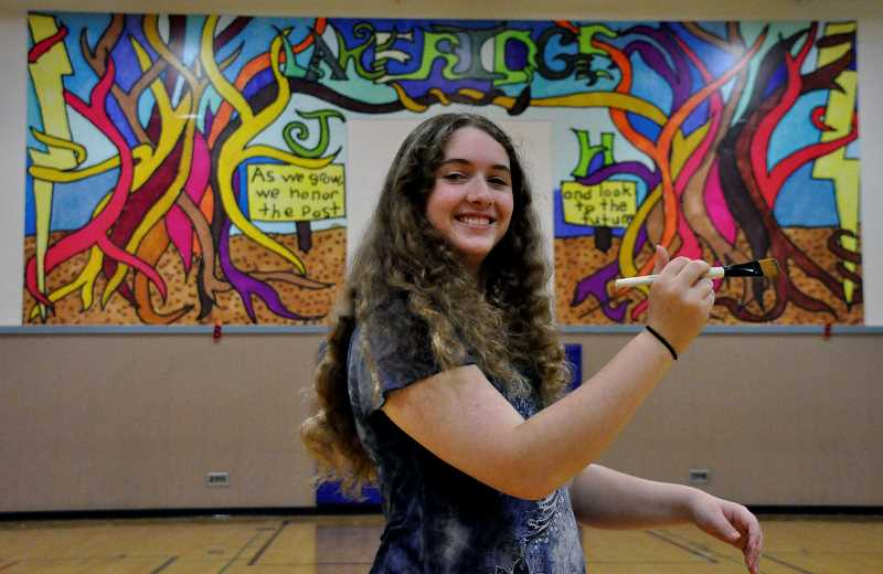 Photo Credit: SUBMITTED PHOTO: KAREN OSTER - Karen Oster captured a photo of her 14-year-old daughter, Sidney, who created the mural that now adorns Lakeridge Junior High Schools gym. Sidney objected to holding a paintbrush because she used markers, but her mom explained that it would be cute.