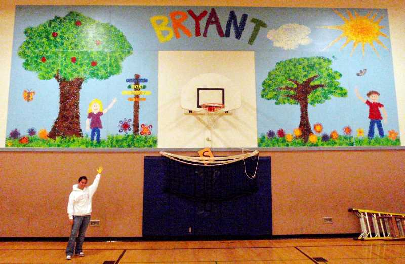 Photo Credit: SUBMITTED PHOTO - Betsy Reid, who was an artist-in-residence at Bryant, poses by the mural she created for the school gym in 2010.