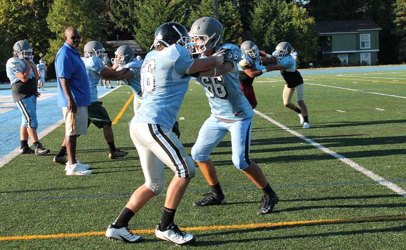 Photo Credit: REVIEW PHOTO: JILLIAN DALEY - Lakeridge player Beau Bryant, left front, and Jack Holum practice their moves Tuesday while defensive line coach coach Tim Price looks on.