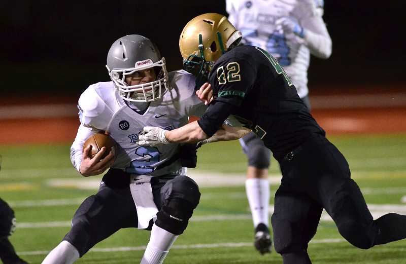 Photo Credit: REVIEW FILE PHOTO: VERN UYETAKE - Lakeridge quarterback Eric Dungey tries to avoid a Jesuit defender during the Pacers season-ending loss in the 2013 playoffs.