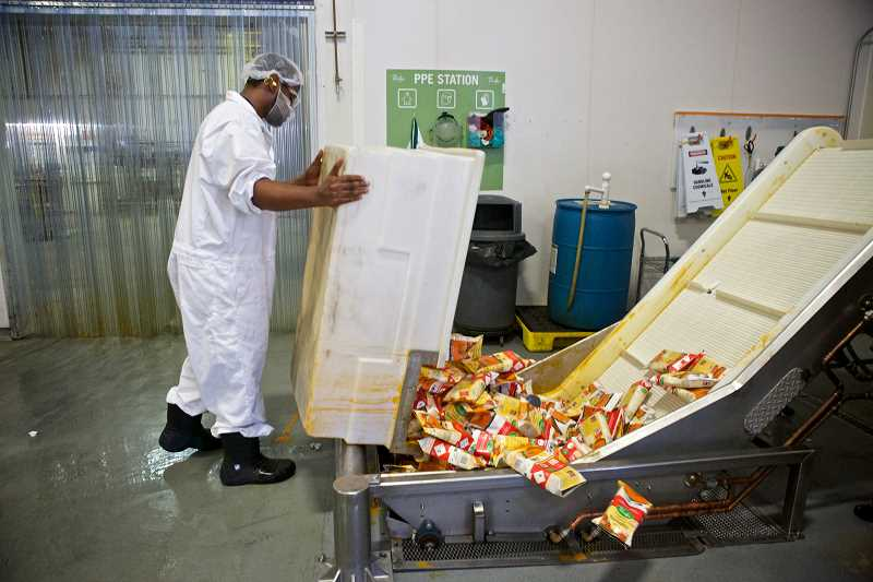 Photo Credit: TIMES PHOTO: JAIME VALDEZ - An employee unloads cartons at the washing station at Pacific Natural Foods.