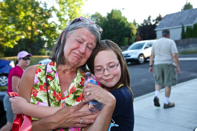 Photo Credit: TIMES PHOTO: JAIME VALDEZ - Colleen Lane receives a hug from Emma Gibson, 11, at the conclusion of the Hansen Ridge Park grand opening event on Tuesday evening. For decades, Lane's grandparents, Harry and Ida Hansen, ran a potato and dairy farm on land where the park sits.