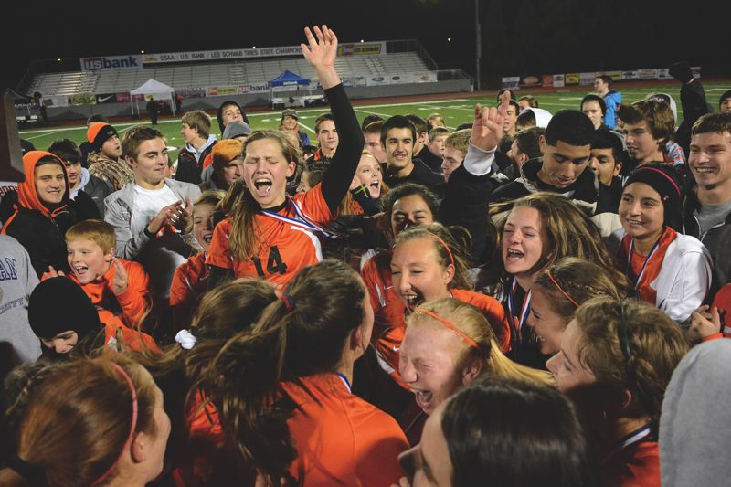 Photo Credit: JOHN WILLIAM HOWARD - Tribe forward Eleanor Jones is surrounded at midfield to celebrate the 2013 state title at Liberty High School, a 3-1 win over La Grande. It's a feeling that the team has yet to forget, and something they use as motivation toward repeating as state champions.