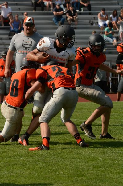Photo Credit: JOHN WILLIAM HOWARD - Scappoose senior running back Johnny Tardiff fights through a tackle during a team scrimmage on Aug. 23. Tardiff is likely to be one of the team's featured backs in an offense based on the running game.