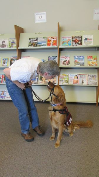 Photo Credit: COURTNEY VAUGHN - Teresa Malarkey of Scappoose interacts with Hero, a service dog in training, at the Scappoose Library. Malarkey is a volunteer dog trainer with PAVE, a nonprofit organization that pairs service dogs with people living with PTSD.