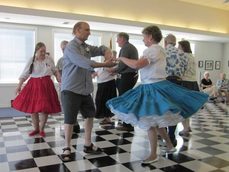 Photo Credit: BARBARA SHERMAN - DO-SI-DO - Sandy Bergeron (in red skirt) and Mary Davis (in blue skirt) dance during a demonstration by members of the Tri Squares Square Dance Club at the Highlands Clubhouse on Aug. 10.