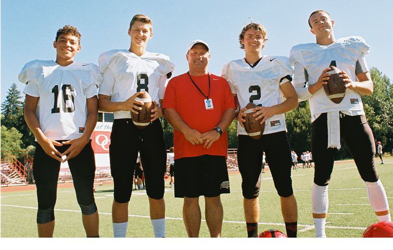 Photo Credit: JOHN DENNY - Its been a competitive battle for the starting nod at quarterback for Oregon City this fall, with four athletes in the mix. Pictured with first-year Oregon City head coach Randy Nyquist are quarterback contenders (from left) sophomore DeQuahn Dennis-Lee, senior Scott Lloyd, junior Riley Rexine and senior Thomas Hamilton.