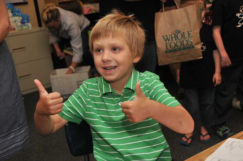 Photo Credit: REVIEW PHOTO: VERN UYETAKE - Sam Coulter gives two thumbs up to his dad on the first day of second grade at Hallinan Elementary.