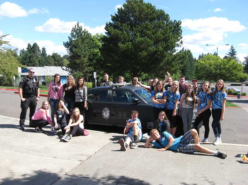 Photo Credit: SHERWOOD POLICE DEPARTMENT - Sherwood High School students stand in front of the revamped patrol car of Kris Asla, the school resource officer at the school.