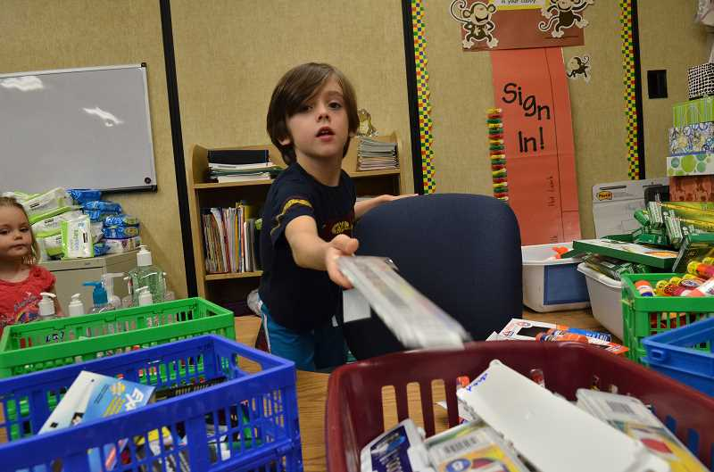Photo Credit: REVIEW PHOTO: VERN UYETAKE - Laimis Hainley unloads his school supplies on his first day of first grade at Hallinan.
