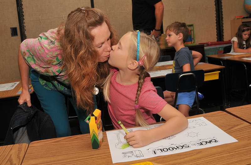 Photo Credit: REVIEW PHOTO: VERN UYETAKE - Helena Huettemeyer gives her mom Renee Huettemeyer a goodbye kiss on the first day of first grade at Hallinan Elementary.