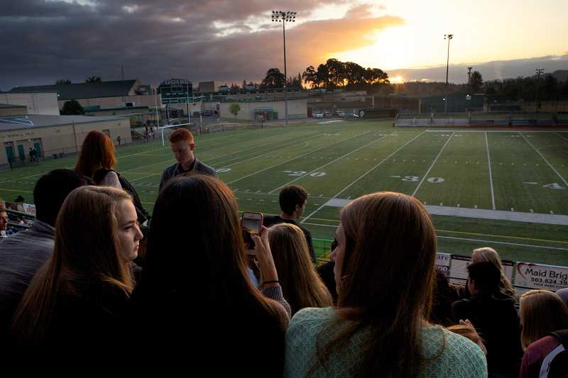 Photo Credit: TIMES PHOTO: JAIME VALDEZ - Leah Perez, center, snaps a photo of the morning sunrise with friends Emily Stentz, left, and Ellory Doolin, right. The trio are part of a yearly tradition at Tigard High to watch the sunrise on the first day of senior year. The students will return to watch the sunset on the evening before graduation.