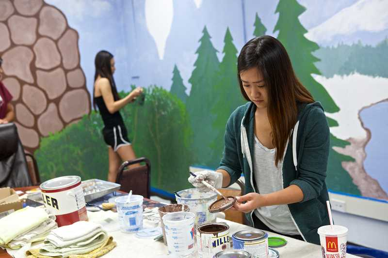 Photo Credit: TIMES PHOTO: JAIME VALDEZ - Jessie Li, a member of Tigard Highs Key Club leadership team, mixes paint for a large mural at Tigard Senior Center.
