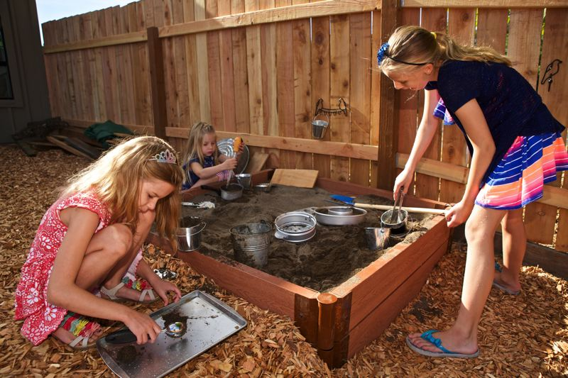 Photo Credit: TIMES PHOTO: JAIME VALDEZ - Ella Murry, 8, left, and her sisters, Leah, 5, Victoria, 10, play in the sandbox in the new playground at St. Gabriel the Archangel Episcopal Church in Bethany.