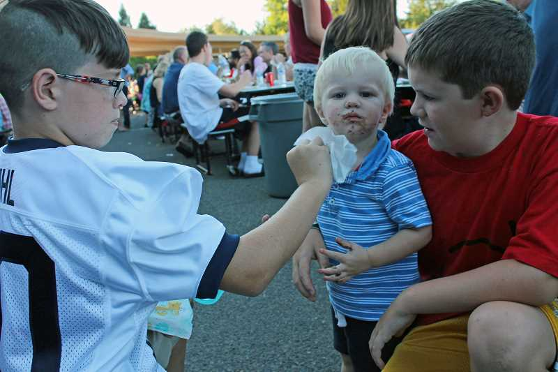 Photo Credit: REVIEW PHOTOS: JILLIAN DALEY - At the Lake Oswego Junior High barbecue,  2-year-old Matthew Duhl gets an impromptu face washing from cousin Aiden Duhl, left, and brother Nathan.