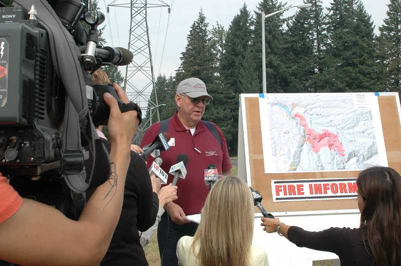 Photo Credit: ESTACADA NEWS PHOTO: ISABEL GAUTSCHI - Bruce Holloway, an incident commander of the 36 Pit Fire Incident Management Team talks to reporters Wednesday morning. Holloway said weather conditions have improved for fighting the fire. Responders are prioritizing halting the fire from spreading on the north and west flanks. Locals should expect to see smoke from controlled burnouts today.