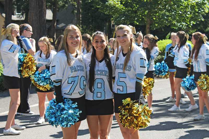 Photo Credit: REVIEW PHOTO: JILLIAN DALEY - Cheer team captains gear up for the parade (from left): Catheryn Apsey, Keana Pigg and Mack Larson. All are seniors.