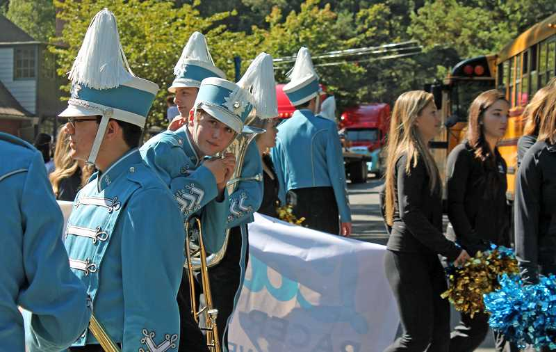 Photo Credit: REVIEW PHOTO: JILLIAN DALEY - A member of the Lakeridge band fastens his hat strap before the homecoming parade.