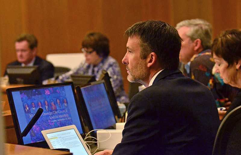 Photo Credit: REVIEW: VERN UYETAKE - City Councilor Jon Gustafson (foreground) listens to a second night of Wizer Block testimony Tuesday. The council was expected to vote on the project Wednesday night.