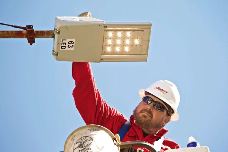 Photo Credit: TRIBUNE PHOTO: JAIME VALDEZ - Eric Bainbridge, apprentice lineman with Christenson Electric Inc., turns on the power switch of am LED fixture  he installed after removing a high pressure sodium street light in Woodstock.