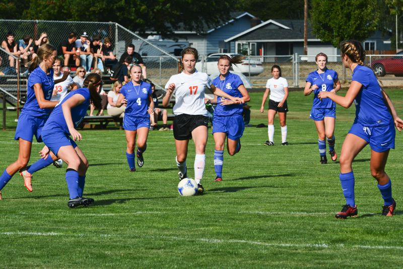 Photo Credit: JOHN WILLIAM HOWARD - Scappoose midfielder Lucy Davidson draws the atttention of four defenders during the Indians' win over La Salle on Sept. 9.