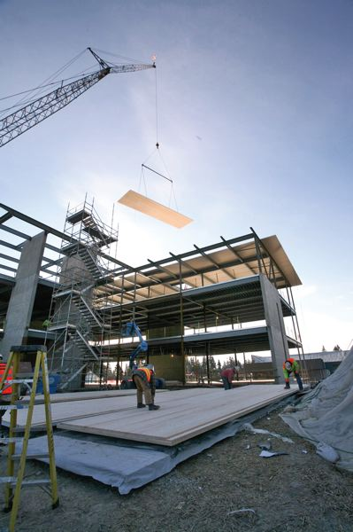 Photo Credit: PHOTO BY SHELLY LANGTON, COURTESY OF KPFF CONSULTING ENGINEERS  - A crane operator lifts a massive sheet of cross-laminated timber into place atop the Shoreline Medical Clinic in Washington.