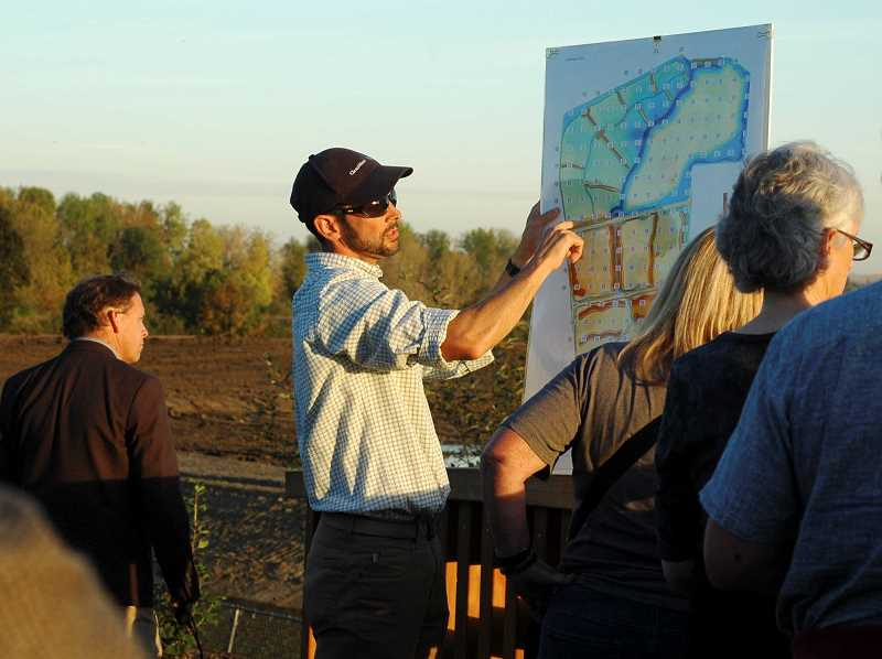 Photo Credit: NEWS-TIMES PHOTO: JOHN MYERS - John Dummer explains a topographical map of the South Wetland project to members of the Fernhill Wetlands Advisory Council. The former flat-bottomed sewage lagoons are now heavily contoured for both hydraulic and habitat purposes. Raised, higher-elevation earth is noted in blue and green while lower-elevation troughs and valleys are noted in orange and red.