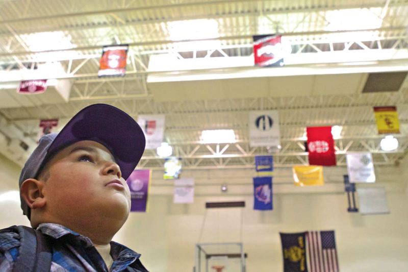 Photo Credit: TRIBUNE PHOTO: JAIME VALDEZ - Alder School student Fred Jiminez looks up at the banners from colleges across the country hanging from the rafters of the school gym. As much as 60 percent of students in I Have A Dream adopted classes have gone on to post-high school education. But adopting an entire school is presenting the foundation with new challenges.