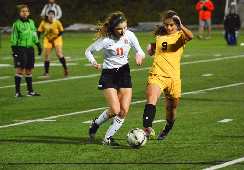 Photo Credit: JOHN WILLIAM HOWARD - Scappoose junior Lauren Frank looks to outrun Cascade senior captain Mary Teubner in the waning moments of the semifinal match. Cascade scored with 14 seconds remaining to snatch the finals berth away from the Indians.