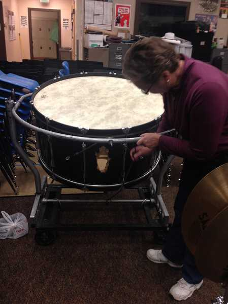 Photo Credit: TIMES PHOTO: GEOFF PURSINGER - Music teacher Kati McKee adjusts a bungee cord holding up a large bass drum. The drums bolt fell off after it was used too much, resulting in a fist-sized hole.