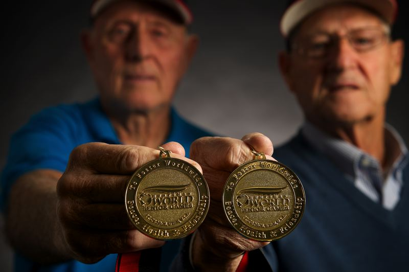 Photo Credit: THE OUTLOOK: TROY WAYRYNEN - Jerry Ross and John Keller both Gresham residents display the gold medals they won in the 80-and-older softball bracket at the World Senior Games last month in St. George, Utah.