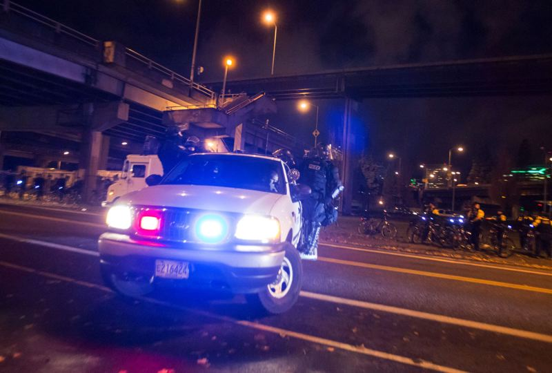 Photo Credit TRIBUNE PHOTO JONATHAN HOUSE - A Portland police truck carrying SWAT team members leaves the scene of protests under the Morrison Bridge. & Pamplin Media Group - Ferguson protests turn chaotic in Portland
