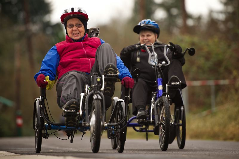 Photo Credit: OUTLOOK PHOTO: TROY WAYRYNEN - Gwen Kleeman, left, along with her 7-year-old dog, Funny, and Judy Williams ride bikes on the Gresham Springwater Corridor Trail.