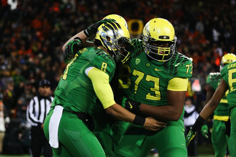 Photo Credit: COURTESY OF DAVID BLAIR - Marcus Mariota (left) receives congratulations from his Oregon Ducks teammates, including offensive lineman Tyrell Crosby.