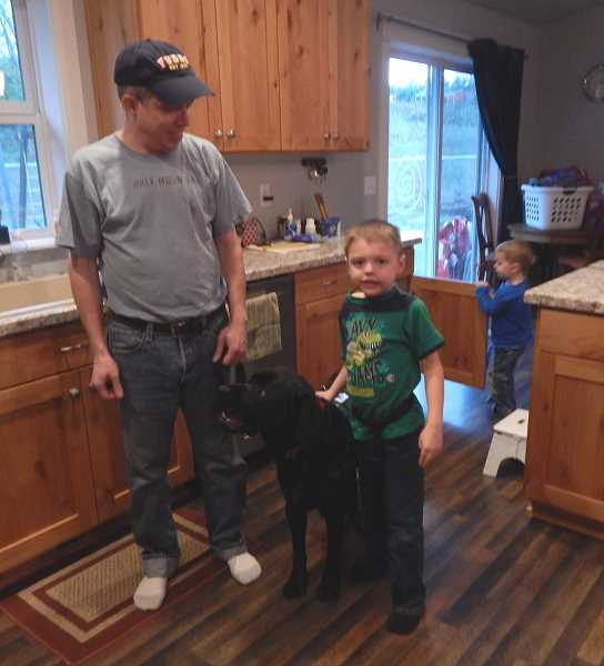 Photo Credit: GAZETTE PHOTO: BARBARA SHERMAN - Under Scott McDonald's supervision, his 6-year-old son John walks through their Sherwood home attached to his autism service dog Kai while little brother Wesley plays in the background.
