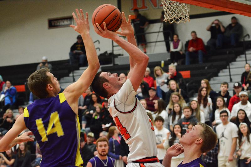 Photo Credit: JOHN WILLIAM HOWARD - Scappoose senior Chase Johnson looks to score past the outstretched hand of Marshfield's Malio Favalora in the second half of the Indians' 53-47 loss on Friday night.