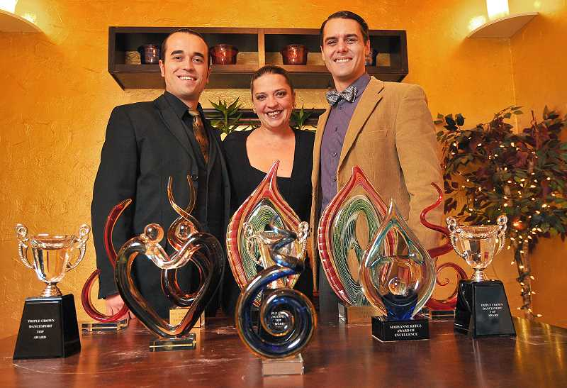 Photo Credit: STAFF PHOTO: VERN UYETAKE - Stas Trilisky (from left), Kristy Higgins and Drew Dyson stand behind the many trophies Step It Up Studio won at the Northeastern Triple Crown Dancesport Championship i