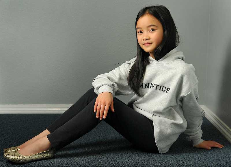 Photo Credit: REVIEW, TIDINGS PHOTO: VERN UYETAKE - Portrait of a gymnast. Raynah Cheng proved to be a fast healer and a terrific competitor when she won her third straight state gymnastics title.