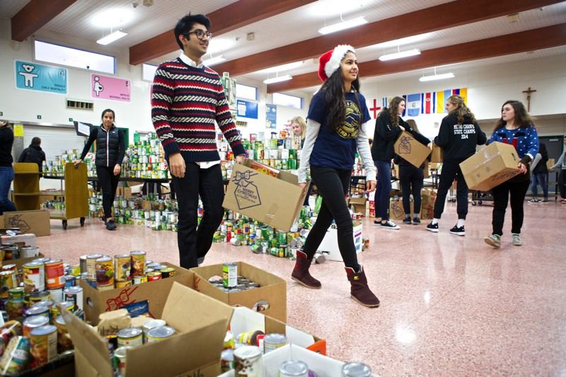 Photo Credit: TIMES PHOTO: JAIME VALDEZ - Jesuit High School students work to pack meal boxes for families in need.