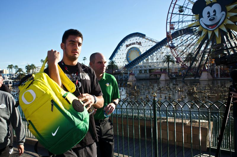 UO quarterback Marcus Mariota (left), followed by coach Mark Helfrich, takes his bag as he gets ready to go on a ride at Disneyland.