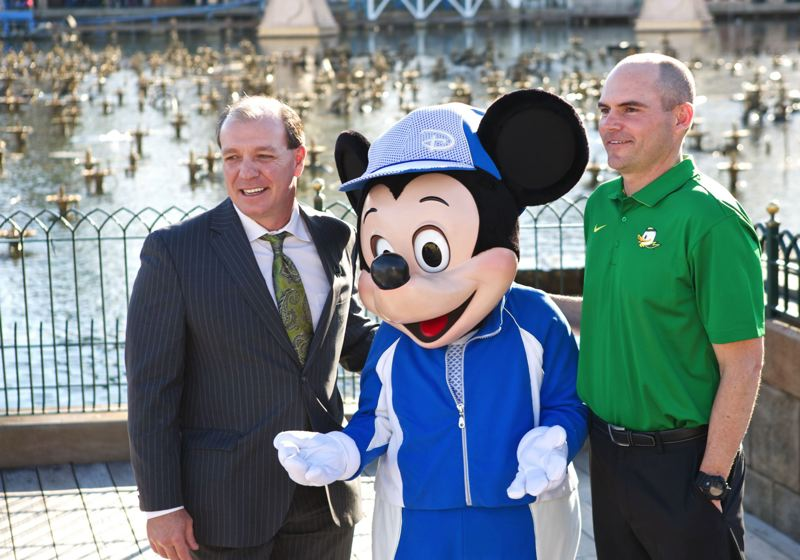 Coaches Jimbo Fisher (left) of Florida State and Mark Helfrich (right) of Oregon get some Rose Bowl advice from Mickey Mouse.