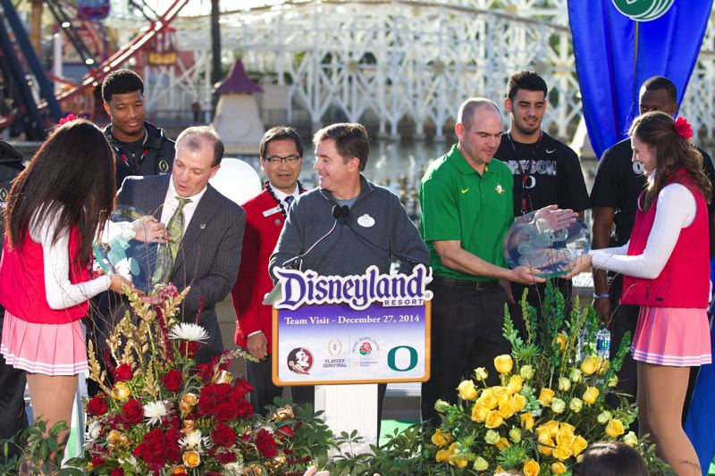 Jimbo Fisher, Florida State coach, and Mark Helfrich, Oregon coach, receive plaques during their teams' visit to Disneyland. Quarterbacks Jameis Winston and Marcus Winston stand behind their coaches.